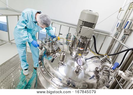 bended scientist in blue lab suit work with big chromed tanks stock photo