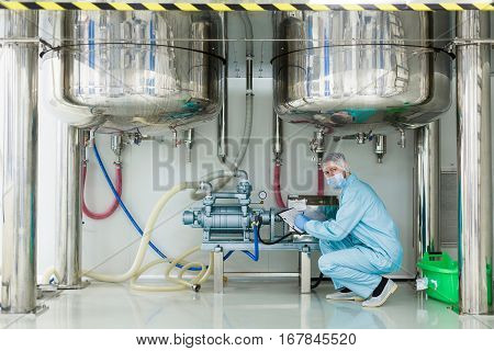 caucasian scientist in blue lab suit sit under big steel barrels work with blue engine look at camera stock photo
