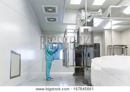 caucasian scientist in blue lab uniform make notes about big steel machine with control panel white barrels on front clean room look at camera stock photo