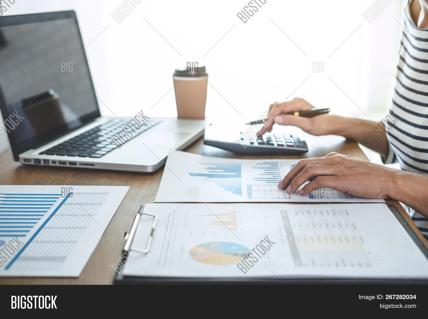 Female Accountant Calculations, Audit And Analyzing Financial Graph Data With Calculator And Laptop