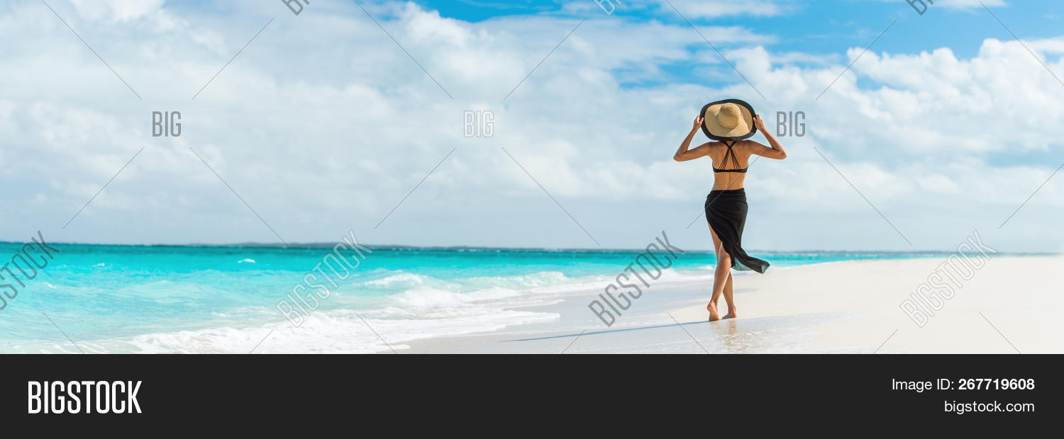Luxury travel summer beach vacation woman walking in black beachwear skirt and hat on paradise white