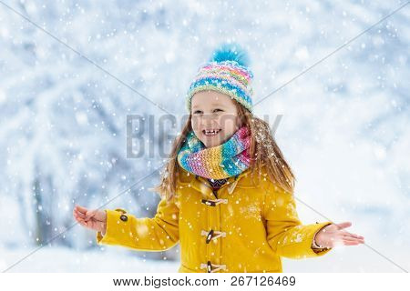 Child in knitted hat playing in snow on Christmas vacation. Winter outdoor fun. Knitting and outerwear for family. Kids play in snowy park. Little girl in knit scarf and mittens catching snowflakes. stock photo