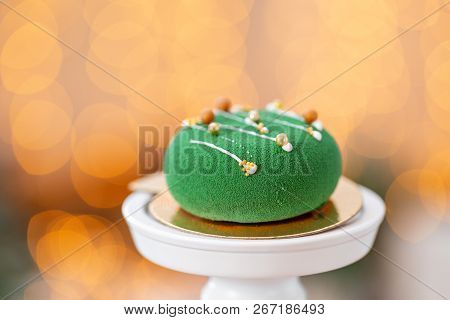 Mini mousse pastry dessert with green velour on garland lamps bokeh background. Modern european cake. French cuisine. Christmas theme stock photo