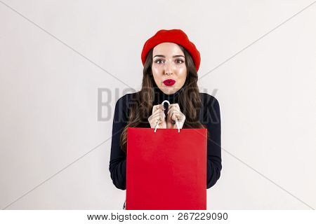Beautiful hipster young woman with bright red lipstick makeup, wearing black turtleneck, mom jeans & red beret, holding blank shopping bag. Autumn holiday sale season concept. Background, copy space stock photo
