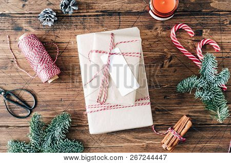 Christmas gift box, presents, dark background with holiday decoration, christmas candy, red and white tape on reel, candle, vanilla sticks and fir branch, holiday card, tag mockup, flat lay. stock photo