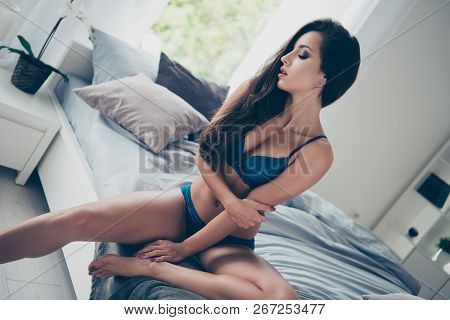 Attractive pretty dreamy charming lovely brunette lady in blue lace with long straight hair hug herself turn head aside and close eyes in cozy house with modern interior stock photo