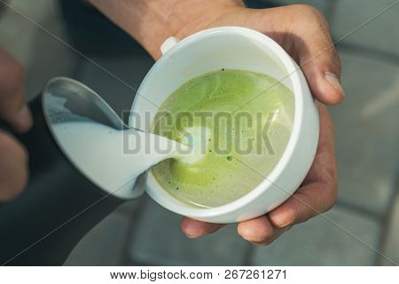 barista pour milk in japanese tea drink. it tastes delicious. perfect morning with green coffee. matcha latte tea ceremony, pour milk. relax in cafe or coffee shop and drinking. Relaxing at home. stock photo