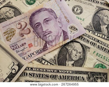 singaporean banknote of two dollar and american dollar bills, background and texture stock photo