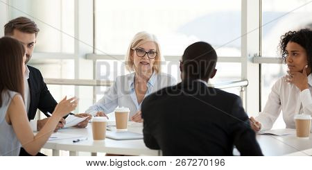 Diverse employees negotiate during business meeting in office stock photo