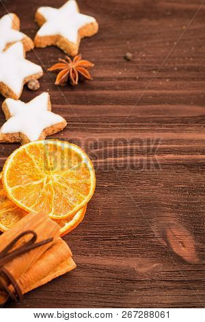 Winter theme. Christmas tea with spices, cup of tea with orange, cinnamon, anise, cookies in a shape of star, pepper, fir cones and gray scarf on wooden background. Flat lay, View from above. Copy space for text. stock photo