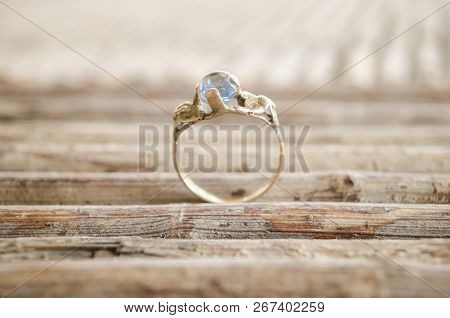 ornate engagement ring on a pattern with natural wood sticks, lines pattern made of natural wood sticks, proposal of love concept stock photo
