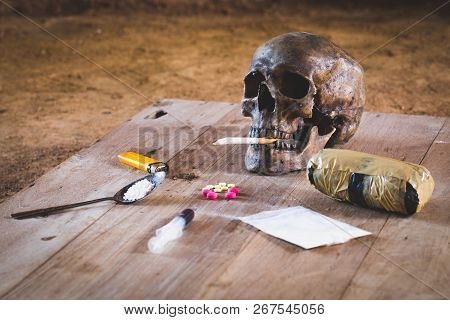 Drugs of various kinds and human skulls on the wooden table, Collection of different hard drugs Heroin, Pills, Tobacco,The concept of death from drugs stock photo