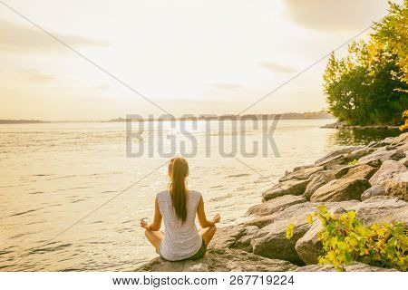 Yoga class outside in nature park by lake river shore. Woman sitting in lotus pose meditating by the
