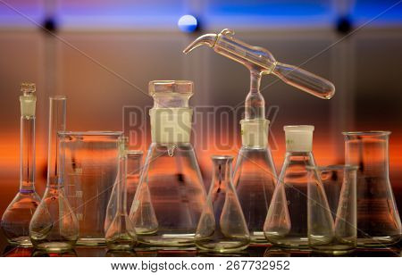 Empty chemical glassware on color background. Group of laboratory empty flasks   on color scientific background reflection on a table stock photo