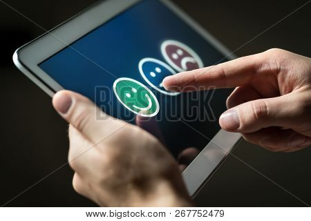Man Using Tablet To Give Review, Opinion And Feedback To Survey, Poll Or Questionnaire For User Expe