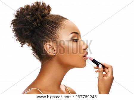Beautiful girl applying lipstick on her lips. Photo of african american girl in profile on white background. Skin care and beauty stock photo