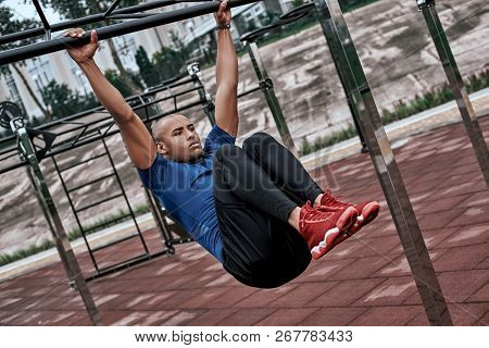 African man is doing stretching exercises at open air gym near the park stock photo