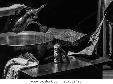 Female hand pours water from jug to copper basin. Vintage barber or shaver tools on wooden table. Old razors with blades, scissors, axe, brush and towel in barbershop or hairdressing saloon stock photo