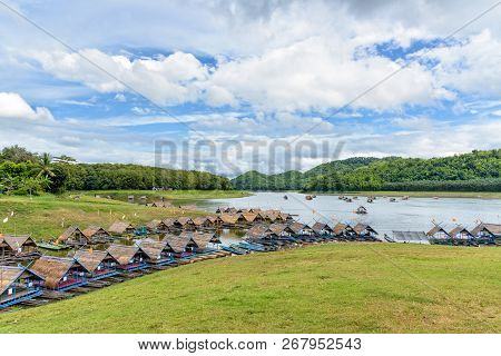 Nameplate of Huai Krathing at Loei on the grassy hill and bamboo raft shelter are floating restaurant in the middle of water under the blue sky as a tourist attraction in Thailand stock photo