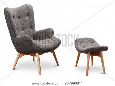 Gray color armchair and small chair for legs. Modern designer armchair on white background. Textile armchair and chair. Series of furniture stock photo