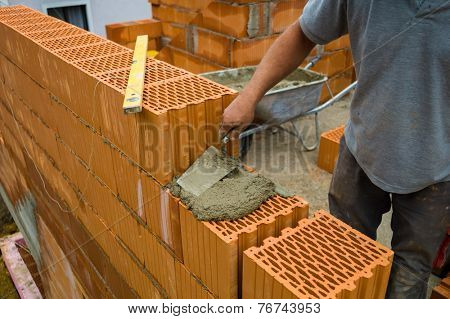 anonymous construction worker on a building site when building a house built a wall of bricks. brick wall of a solid house. icon image for undeclared work and bungling stock photo