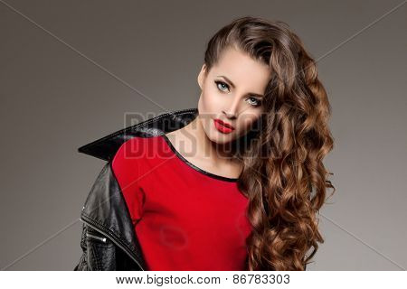 Beautiful young woman model brunette with long curled hair with red lips in leather jacket. Girl wav