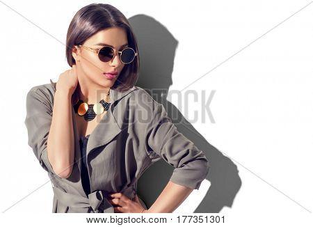 Beauty Fashion brunette model girl wearing stylish coat and sunglasses. Sexy woman portrait with per