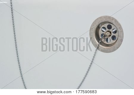 Overflow-prevention device with lead and chain in bathtub stock photo