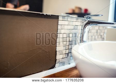 Close up details of renovation works. Bathroom details with mosaic tiles and cement adhesive stock photo