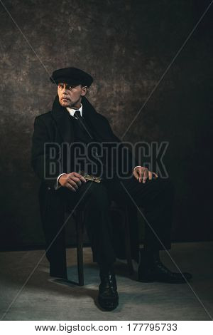 Retro 1920s english gangster with gun sitting on chair. Peaky blinders style. stock photo
