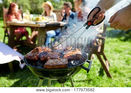 leisure, food, people and holidays concept - man cooking meat on barbecue grill for his friends at s