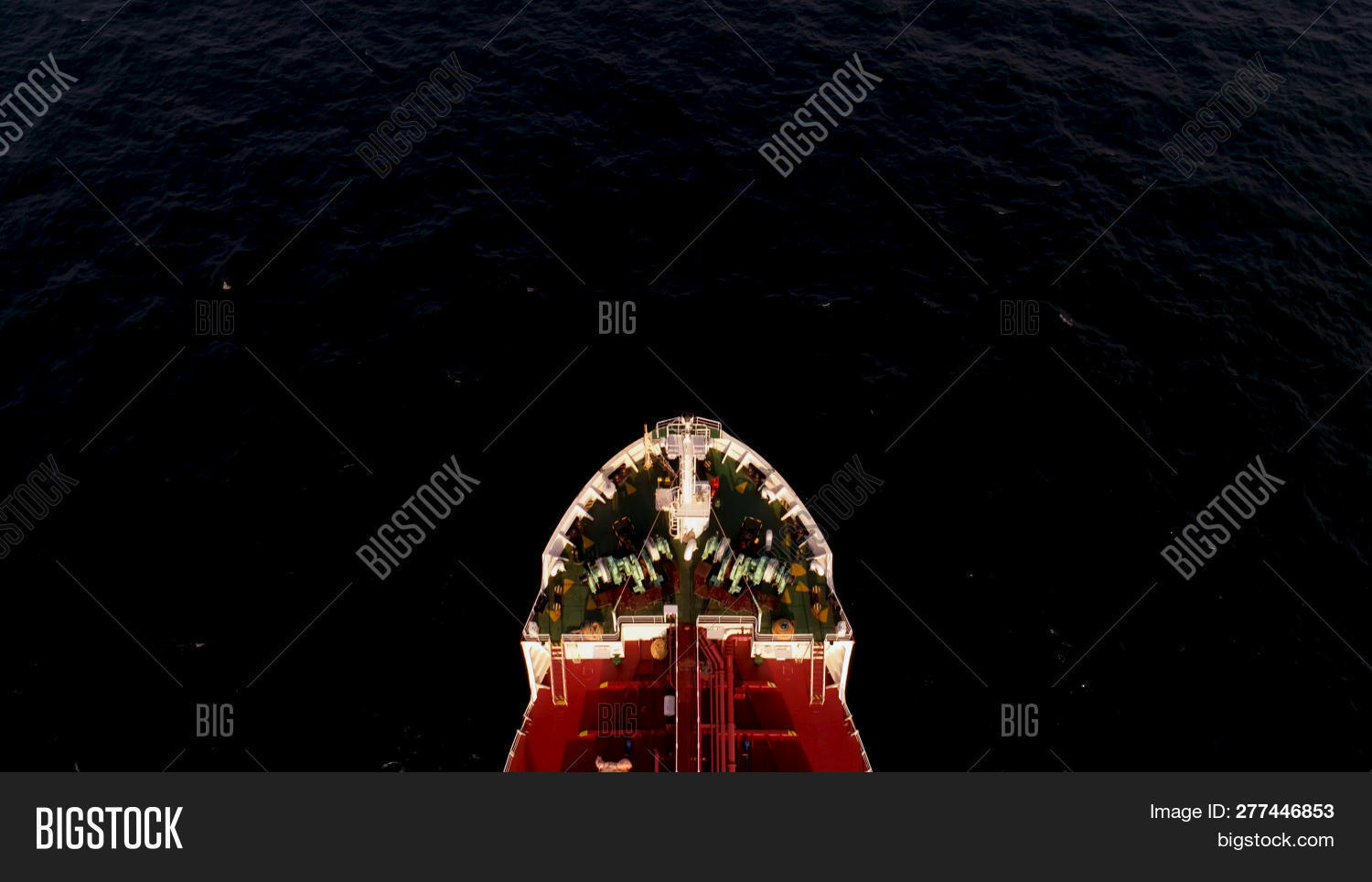 Singapore - 25 September 2018: Aerial view of big red container or cargo ship on blue sea and sky backgroung. Shot. Top view of large red barge sailing in the sea.