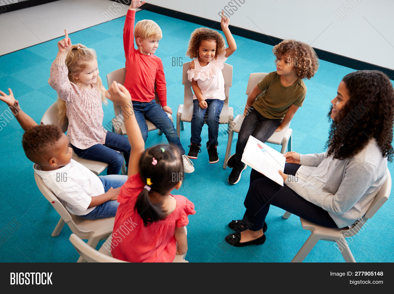Young female school teacher reading a book to infant school children, sitting on chairs in a circle