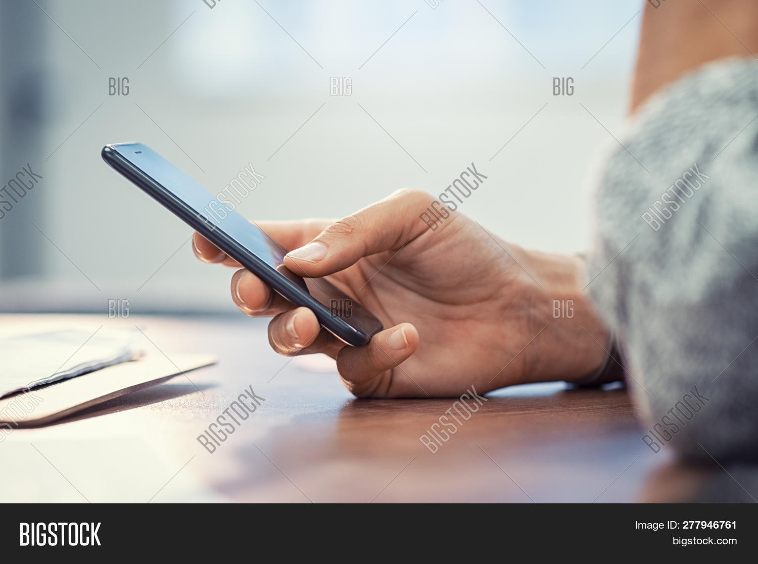 Closeup hand of woman using smartphone on wooden table. Businesswoman typing text message on smart p