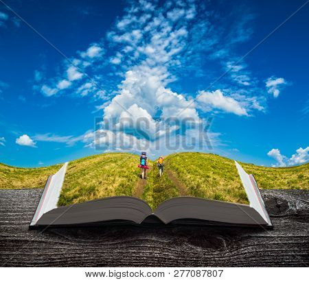 Family of hikers on a trekking on the pages of an open magical book. Majestic landscape. Travel and education concept. stock photo