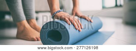Yoga at home active lifestyle woman rolling exercise mat in living room for morning meditation yoga banner background. stock photo