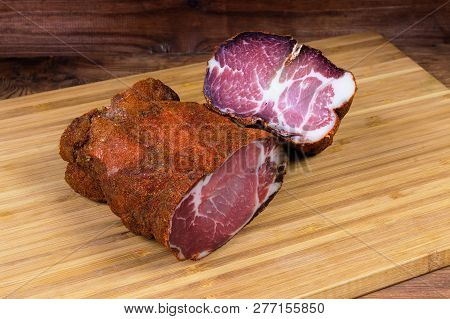 Two pieces of dried pork made of neck with balanced quantity of white fat on the bamboo cutting board on a dark colored wooden rustic table stock photo