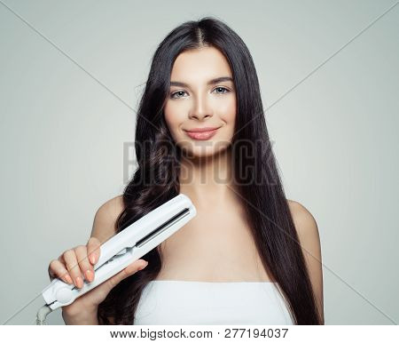 Beautiful woman with straight hair and curly hair using hair straightener. Cute girl straightening healthy hair with flat iron. Hair care concept stock photo