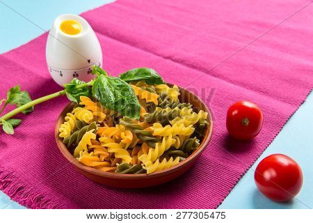 Uncooked Italian pasta Fusili with tomatoes and basil in a ceramic plate stand on a maroon napkin with a kitchen timer on a light blue background, close-up stock photo
