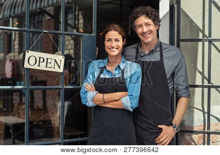 Two cheerful small business owners smiling and looking at camera while standing at entrance door. Ha
