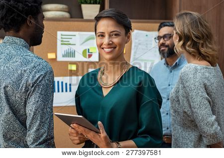 Portrait of glamour business woman looking at camera with colleagues working in background. Successf