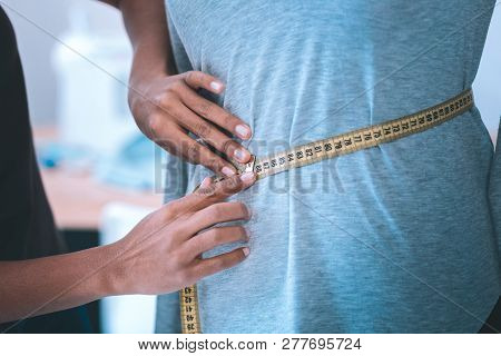 View of seamstresses hands measuring clients waist stock photo
