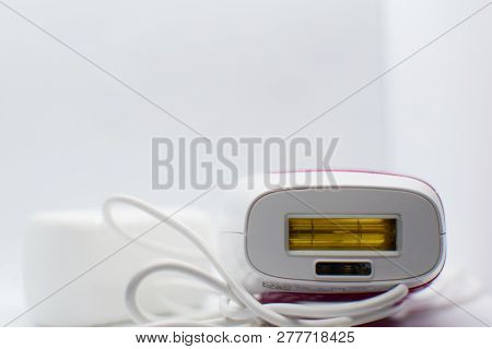 Personal laser epilator device with cable for hair removal on white background with copy space for text. stock photo