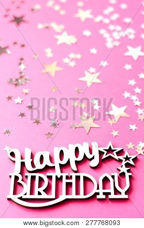 The wooden inscription Happy Birthday on a pink background with silver stars. stock photo