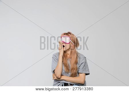 Studio portrait of bored teenager in grey t-shirt covering mouth with hand, looking left/drowsiness, sleepiness, yawn, slackness, bored, tired, suffering from lack of sleep, early wakeup/ isolated. stock photo