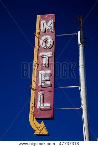 A vintage motel sign with an arrow in frount of blue sku stock photo