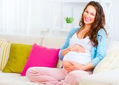 Pregnant Happy grinning Woman sitting on a couch and stroking her paunch. Mother Expecting Baby. Pre