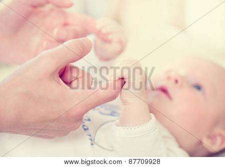 Parent holding newborns hand. Hand in hand. Mother and her Newborn Baby. Happy Mother and Baby toget