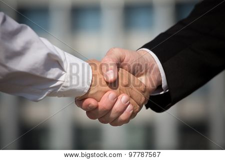 Business handshake, the deal is finalized between two enterprises. Man in black suit and woman in white one have signed the agreement. stock photo