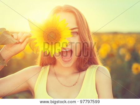Beauty joyful teenage girl with sunflower enjoying nature and laughing on summer sunflower field. Su